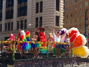 Rainbow attired people with comcast peacock on a platform
