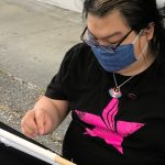 A person wearing blue cloth mask and black T-shirt is doing embroidery on a frame.