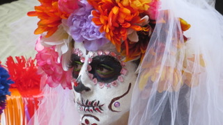 Photograph of person in skull makeup wearing flowers on their head