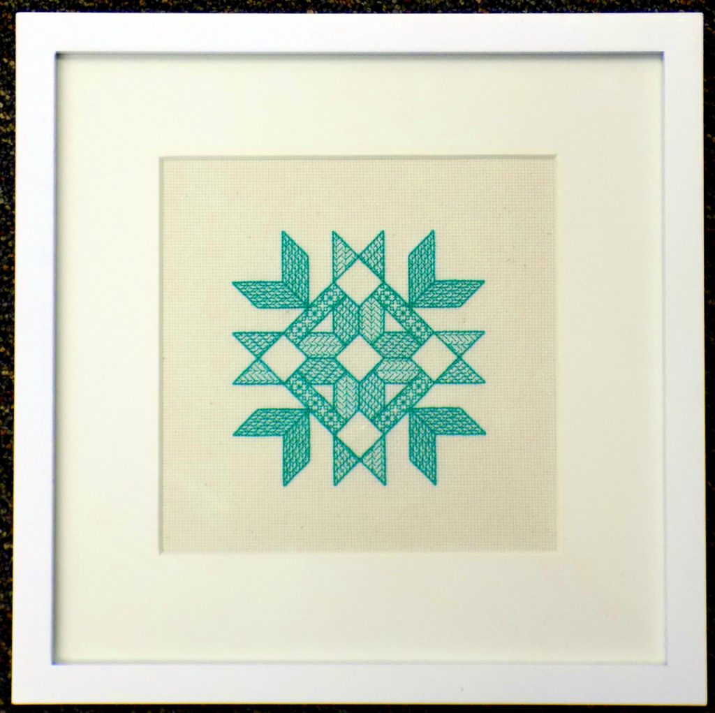 Green embroidery on white background in square frame